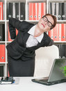 Business woman with pain in her back working at office Royalty Free Stock Photos
