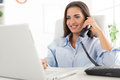 Business woman phoning in office young sitting at an desk front of laptop which looks with a smile on her face Royalty Free Stock Images
