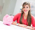 Business woman with a piggybank happy her savings in Stock Photography