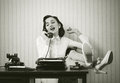 Woman talking on phone at desk Royalty Free Stock Photo