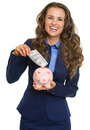 Business woman putting dollars banknote into piggy bank smiling isolated on white Royalty Free Stock Images