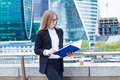 Business woman reading documents folder on the street on a background of skyscrapers Royalty Free Stock Photo
