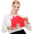 Business woman real estate agent holding red paper house.