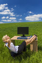 Business woman relaxing office desk green field concept shot of a beautiful young businesswoman with her feet up at a with a Royalty Free Stock Image