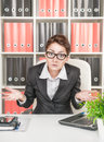 Business woman shrugs in glasses her shoulders at workplace Stock Images