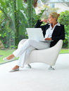 Business woman sitting on a chair with laptop Royalty Free Stock Photography