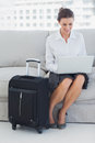 Business woman sitting on the couch smiling using laptop with her suitcase Stock Image