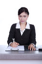 Business woman sitting on her desk holding a pen working with do Royalty Free Stock Photo