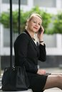 Business woman sitting outdoors with cellphone portrait of a Stock Images