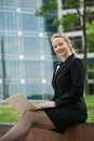 Business woman sitting outdoors and smiling with laptop portrait of a in the city Royalty Free Stock Photography