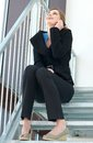 Business woman sitting on the stairs and talking on the phone portrait of a happy during an office break Stock Images