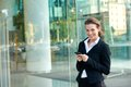 Business woman smiling with cell phone outside office building Royalty Free Stock Photo
