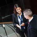 Business woman smiling while talking to businessman