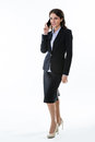 Business woman is speaking by phone on the white background attractive standing and smiling Royalty Free Stock Image