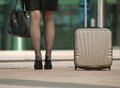 Business woman standing with bag and suitcase on pavement Stock Images