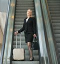 Business woman standing on escalator with travel bags portrait of a rear view Stock Photos