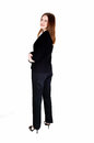 Business woman standing a tall slim young in a black suit from the back looking over her shoulder isolated for white background Royalty Free Stock Images