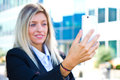 Business woman takes a selfie with her cell phone beautiful Stock Photo