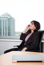 Business woman talking on cell phone young relaxed in chair and in office Royalty Free Stock Image