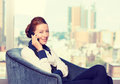 Business woman talking on mobile phone siting in armchair by the office window Royalty Free Stock Photo
