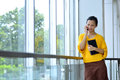 Business woman using cellphone in yellow shirt in the office Stock Photo