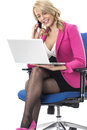 Business woman using a laptop computer and mobile cell phone attractive young Stock Image