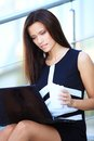 Business woman using laptop on steps outdoors portrait of a smiling young Royalty Free Stock Images