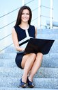 Business woman using laptop on steps outdoors portrait of a smiling young Royalty Free Stock Image