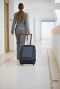 Business woman walking with bag on wheels Royalty Free Stock Photos