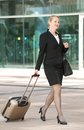 Business woman walking int he city with travel bag and luggage portrait of a Royalty Free Stock Photography
