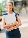 Business woman walking outdoors holding a laptop Stock Photo