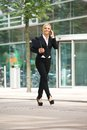 Business woman walking outdoors and talking on mobile phone portrait of a happy Stock Photo
