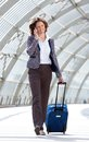 Business woman walking at station with bag and mobile phone Royalty Free Stock Photo