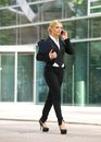 Business woman walking and talking on cellphone in the city portrait of a Royalty Free Stock Image