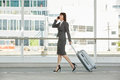 Business woman walking and talking on mobile phone with suitcase Royalty Free Stock Photo