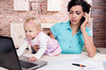 Business woman working her baby girl young women with in the kitchen Royalty Free Stock Images