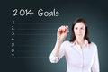 Business woman writing blank 2014 goals list. Blue background. Royalty Free Stock Photo