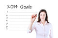 Business woman writing blank 2014 goals list. Isolated on white. Royalty Free Stock Photo