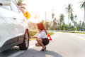 Business women driver changing tyre on her broken car. Royalty Free Stock Photo