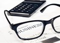 Business word see through glasses lens on financial newspaper near calculator Royalty Free Stock Photo