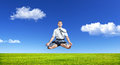 Business yoga businessman doing meditation and levitating under the grass at blue sky with white clouds Stock Photos