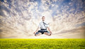 Business yoga levitation businessman doing meditation and levitating under the green grass at sunset sky Royalty Free Stock Images