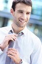 Businessman adjusting his tie portrait of young business man smiling Royalty Free Stock Images