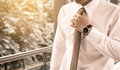 Businessman adjusting necktie before working time. Royalty Free Stock Photo