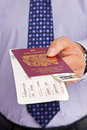 Businessman airport check in close up of a handing over his boarding pass and passport at the tickets are mock ups and all details Royalty Free Stock Photos