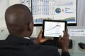 Businessman analyzing graph on digital tablet rear view of young african in office Stock Image