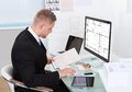 Businessman analyzing a spreadsheet online checking against document in his hand to collate the information Stock Photos