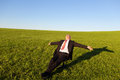 Businessman with arms outstretched on chair in grassy field full length of mature sitting against clear sky Stock Photography