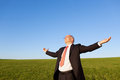 Businessman with arms outstretched standing in field against sky mature clear Stock Photos