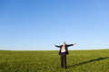 Businessman with arms outstretched standing in field mature against sky Royalty Free Stock Photo